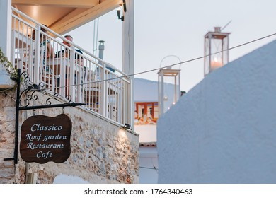 Hersonissos,Crete/Greece - 07.03.2018: A couple of young tourists, taking dinner in town after sun set.  Greek terrace in Hersonissos .