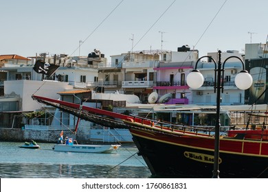 Hersonissos,Crete/Greece - 07.03.2018: Old pirate boat in port, and square greek buildings in background