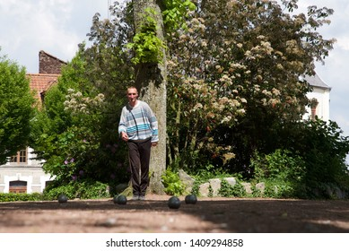 Hesdin, Hauts-de-France/France-May 21 2019: a Pétanque player prepares to throw his boule, or ball in a leafy glade in the market town of Hesdin