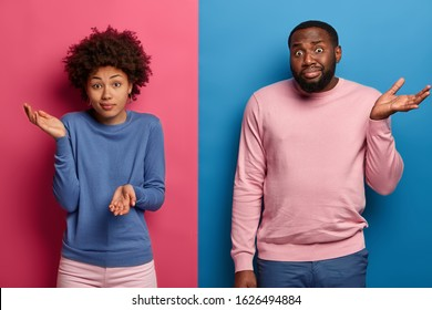 Hesitant questioned black woman and man shrug shoulders with clueless expressions, have no suggestions, spread palms with doubt, make decision, dressed casually, stand over pink and blue wall