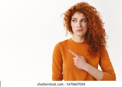 Hesitant worried cute modest redhead curly-haired female, looking pointing left dissatisfied and doubtful, have concern about bad uncertain choice, standing white background disappointed