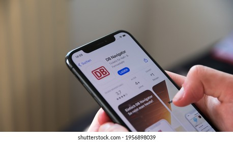 Hessen Germany - April 16,2021:Deutsche Bahn App on the iPhone X. Young man downloading the Train App in Germany