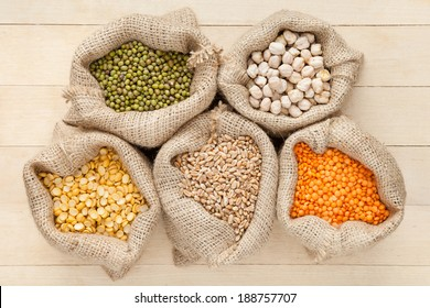 hessian bags with cereal grains: red lentils, peas, chick peas, wheat and green mung on wooden table, top view