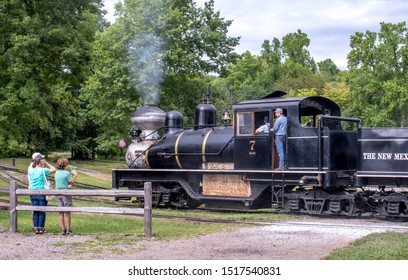 Hesston IN USA ,August 31 2019; tourists cover their ears as a conductor blows a horn on a vintage steam engine, during an event at the Hesston train museum