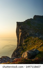 Hesten Mountain ridge at Senja, Norway. Golden light shining from the setting sun. In the backgrund the ocean bathed in yellow sun light. Blue sky, warm colors, shaddows.