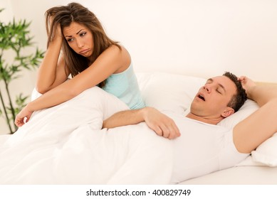 Heterosexual couple in bed, man sleeps and snoring with mouth open, while a tired woman irritated by snoring sitting on bed with head on arm.