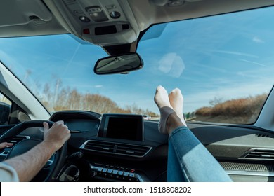 Heterosexual couple in a luxury car, making a road trip, the man has his hands on the steering wheel and the woman has her feet with some socks on top of the dashboard.