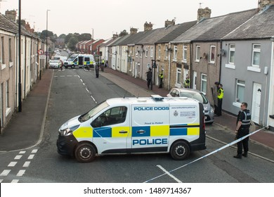 Hetton / Great Britain - August 27, 2019 : Police with vans close of a street with terraced houses to deal with an incident.  Residential setting.