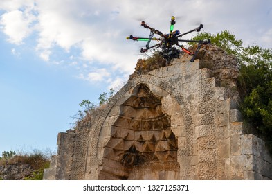 The Hexacopter (Multicopter) drone with the professional camera takes pictures of the historical artifacts. Uav drone copter flying with digital DSLR camera. High resolution digital camera on the sky