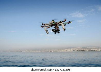 The Hexacopter (Multicopter) drone with the professional camera takes pictures above sea. Uav drone copter flying with digital DSLR camera. High resolution digital camera on the sky.