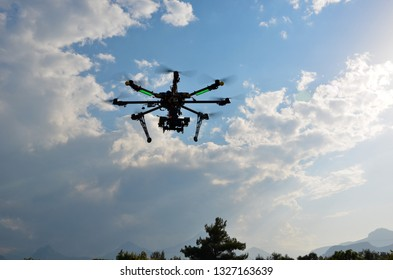 The Hexacopter (Multicopter) drone with the professional camera takes pictures the air. Uav drone copter flying with digital DSLR camera. High resolution digital camera on the sky.