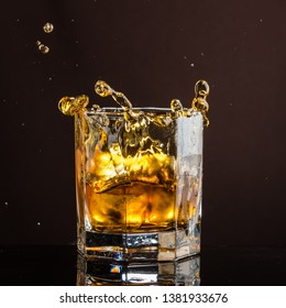 hexagonal glass of whiskey with ice and splashes from an abandoned and falling ice cube