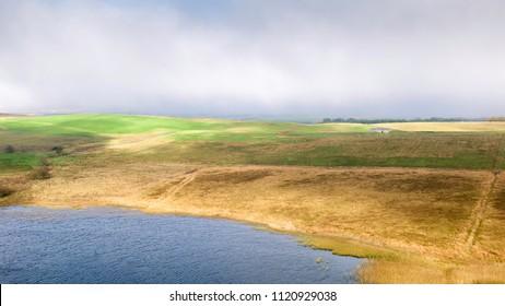 Hexham, Northumberland, UK. Veiw across Crag Lough towards surrounding farmland in Northumberland National Park on a misty morning, Hexham, Northumberland, UK.