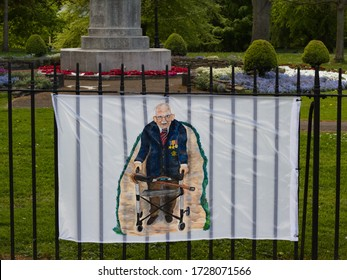Hexham, UK - May 9th 2020: A handrawn banner of Colonel Tom Moore hangs on the railings in front of a war memorial to mark VE Day
