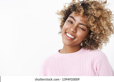 Hey let us enjoy this bright day. Portarit of good-looking carefree and relaxed young beautiful african-american young woman with blond afro haircut winking tilting head and smiling broadly