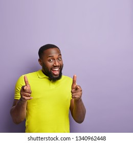 Hey, look at me! Joyful delighted funny black man with thick bristle, makes finger fun gesture with both hands, glad to make choice, wears casual t shirt, stands over purple wall, blank space above