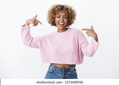 Hey it me who you need. Portrait of happy and enthusiastic good-looking dark-skinned girl with piercing and blond afro hair smiling joyfully suggesting her help pointing at herself joyfully