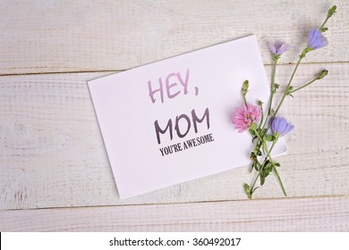 Hey, Mom , Your are awesome message card and bouquet of flowers on rustic wooden table. Funny valentine card for mother, birthday card, funny mother's day card
