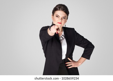 Hey you! Angry boss pointing finger at camera. Studio shot, indoor. Isolated on grey background