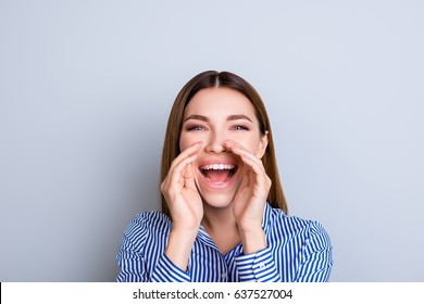 Hey you! Cheerful young lady in smart striped shirt is shouting and holding hands near to open mouth on blue background