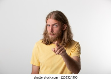 Hey you! Closeup photo of flirty young guy with a beard, mustache, blond hair to the shoulders and blue eyes looking at camera and pointing finger isolated over white background