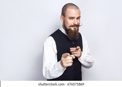 Hey you. Handsome businessman with beard and handlebar mustache looking at camera. studio shot, on gray background.