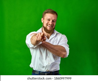 Hey, you. The man shows his fingers in the frame on a green background. You're a winner. Caucasian with a smile. High quality photo