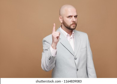 Hey you. Portrait of serious handsome middle aged bald bearded boss businessman in classic gray suit standing and looking at camera, warning. indoor studio shot, isolated on light brown background.