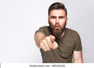 Hey You! Portrait of surprised excited bearded man with dark green t shirt against light gray background. studio shot.