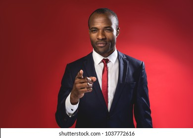 Hey you. Waist-up portrait of serious young african manager is pointing you while standing. Isolated on red background