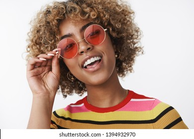 Hey you wanna have fun. Portrait of cool and stylish joyful african american party girl with blond haircut and pierced nose raising head in confident and chill pose smiling, wearing trendy sunglasses
