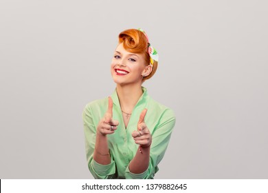 Hey you! Woman red head young woman pretty pinup girl pointing at camera, point index fingers hands like guns gesture isolated on gray background. Retro vintage 50's style Emotion face expression.
