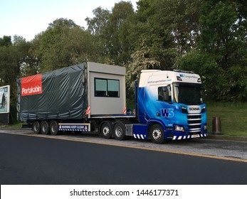 Heywood, Greater Manchester / UK -May 20 2019: WS Transportation Semi-Truck Carrying a Wide Load a Portakabin Module Unit for Delivery to Site on a Flatbed Trailer.