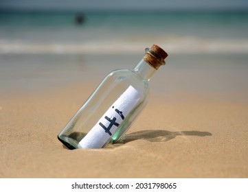 Hi. Bottle on beach with greetings.Hi! Bottle with greetings on beach. Funny holidays. Message in a bottle