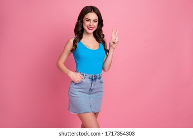 Hi guys. Photo of pretty cheerful lady amazing stylish outfit summer day showing v-sign symbol friends wear casual blue singlet denim short skirt isolated bright pink color background