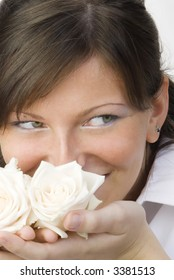 Hi lev is a nice and young woman with roses in her hands smelling and smiling with her fair eyes