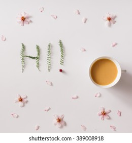 """Hi!"" message made of green grass with cup of coffee or tea and flowers"