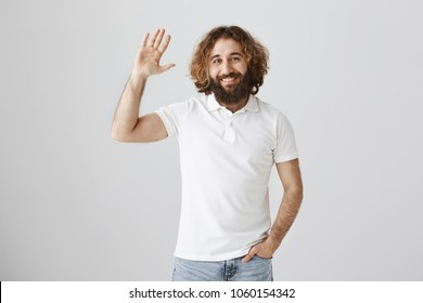 Hi, my friend. Portrait of good-looking ordinary eastern male with curly hair and beard raising hand and waving in greeting gesture, welcoming familiar person on street or giving five to mate