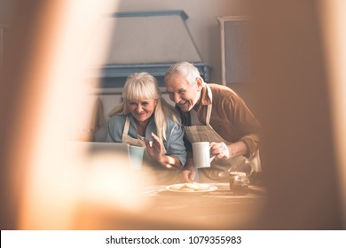Hi. Portrait of happy mature husband and wife having online conversation by modern computer. They are gesturing to camera and smiling. Pensioners are standing in kitchen with cups of tea