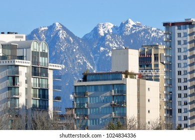 Hi rise, high density towers stand in front of snow capped mountains.