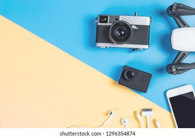 Hi tech travel gadget and accessories on blue and pink copy space with drone action camera
