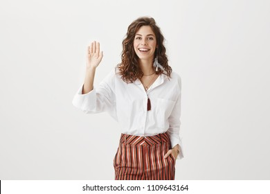 Hi what is up. Portrait of carefree friendly european female entrepreneur, holding hand in pocket and smiling broadly while waving raised palm, greeting friend, meeting with mates from work in cafe