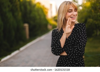 Hi what is up. Young beautiful woman with long short hair congratulating her friend. Portrait of carefree friendly woman, smiling broadly while waving raised palm, greeting friend, meeting with mates.