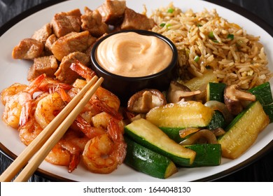 Hibachi dish consisting of fried rice with egg, shrimp, steak and vegetables served with sauce closeup in a plate on the table. horizontal