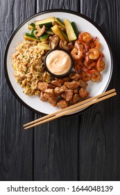 Hibachi dish consisting of fried rice with egg, shrimp, steak and vegetables served with sauce closeup in a plate on the table. Vertical top view from above