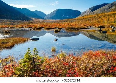 Hibiny mountains reflected in a freshwater lake in the valley of Petrelius stream with colorful tundra bushes and yellow taiga forest in foreground, Kola peninsula above the Arctic circle, Russia