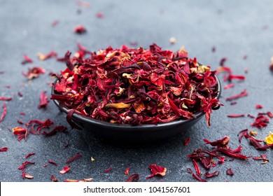 Hibiscus tea in black bowl. Slate background. Copy space.