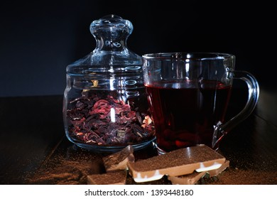 hibiscus tea in a mug and dry tea in a jar on a dark background