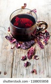 Hibiscus tea in teacup with dry hibiscus flower leaves. Organic herbal cup of tea on vintage wooden table background.
