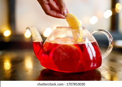 Hibiscus tea in transparent teapot with lemon slice on table. Herbal tea rosella, karkade or red sorrel are fruit tea.